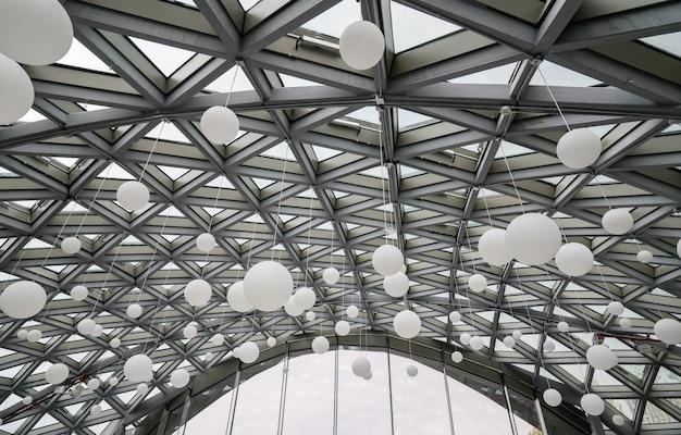 Viele weiße luftballons befinden sich auf dem glasdach des art centers