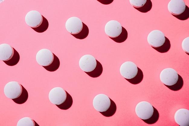 Viele weiße medizinische pillen in einer reihe auf einem rosa hintergrund. pillen werfen einen schatten. pillenmuster