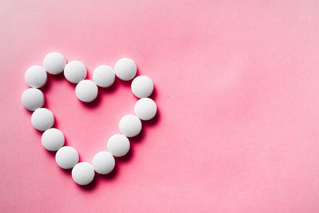 Viele weiße pillen vom herzen auf einem rosa hintergrund. geschenkkonzept annehmen. kardiologie oder liebeskonzept
