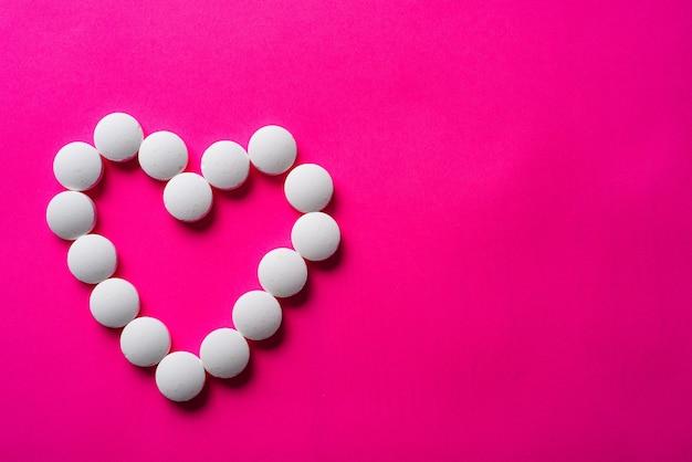 Viele weiße pillen von herzen auf einem rosa