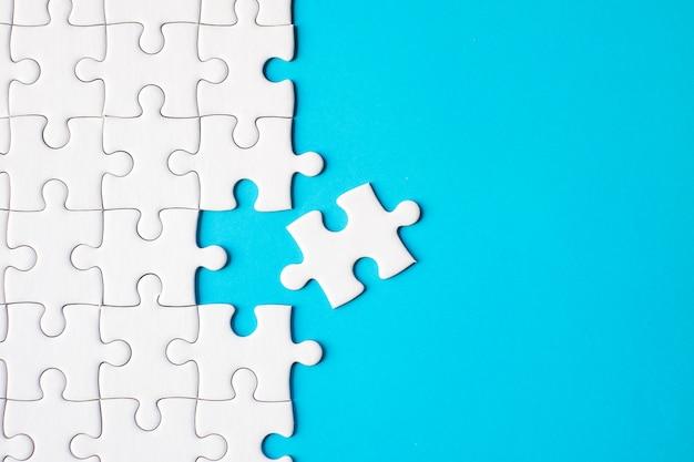 Viele weiße puzzle auf blauem hintergrund - ideenlösungskonzept.