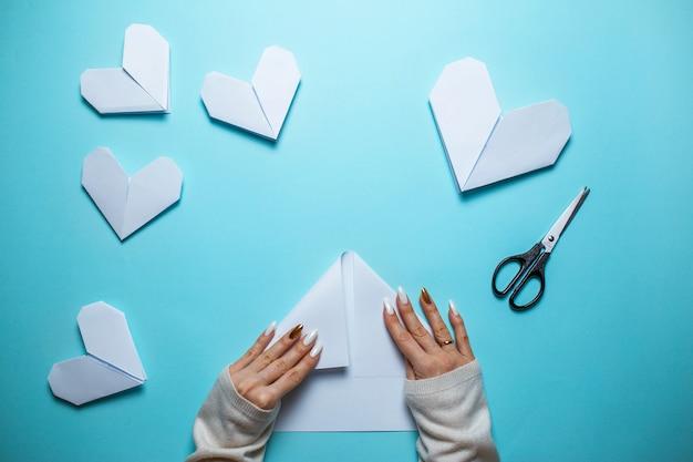 Viele weißen origamiherzen auf blauem hintergrund mit blatt papier und scheren in der mitte. valentinstagkarte mit der frau, die origamiherz auf blauem hintergrund macht.