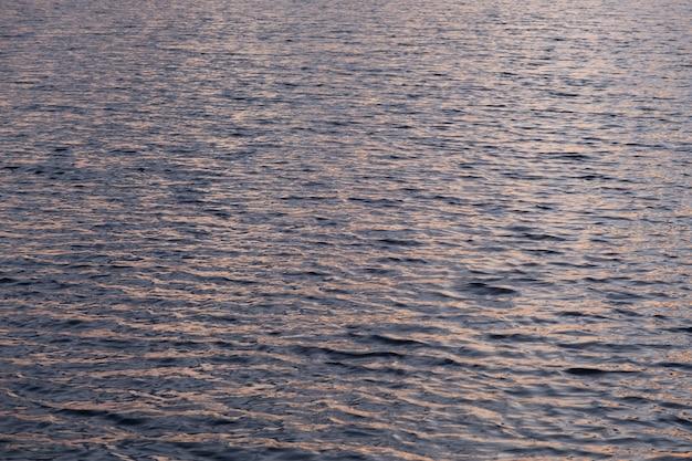 Viele wellen auf der seeoberfläche bei sonnenuntergang timegold wasserbeschaffenheit natürliche sommerhintergrundwellen