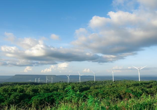 Viele windkraftanlagen auf dem berg mit wald- und talhintergrund mit blauem himmel und bewölktem