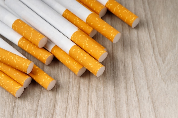 Viele zigaretten werden auf den holzboden gelegt. sie sind gesundheitsschädlich.