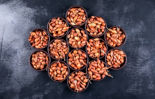 Viele zwiebeln oder schalotten in schalen nebeneinander auf dem tisch. draufsicht.