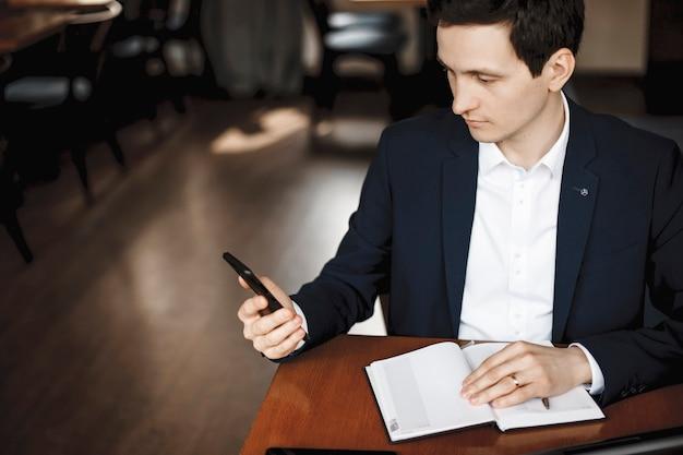 Vielen dank, dass sie mich zum teil gemacht haben. hübsche junge männliche brünette, die ein smartphone hält und auf den bildschirm schaut, während sie mit einer hand auf einem notizbuch auf einem schreibtisch sitzt.