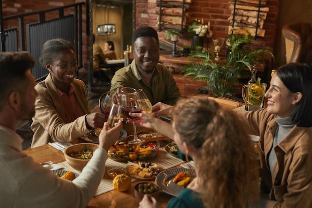 Vielfältige gruppe von menschen klirren gläser, während sie dinnerparty mit freunden und familie in gemütlichem interieur genießen