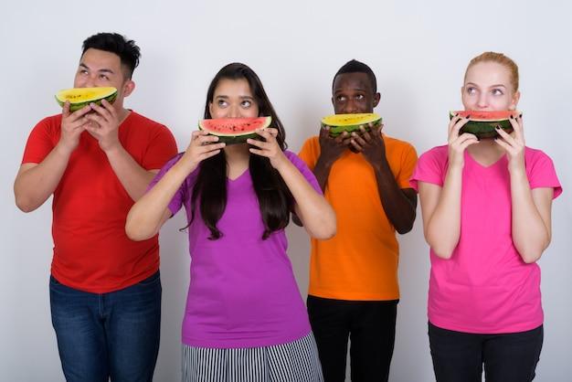 Vielfältige gruppe von multiethnischen freunden, die denken, während sie obst essen