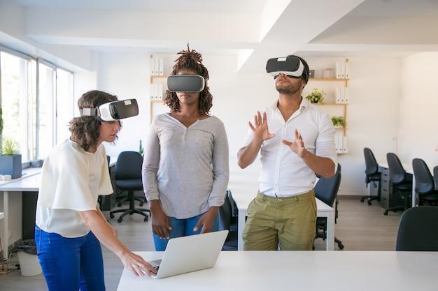 Vielfältiges dreiköpfiges team beobachtet die virtuelle präsentation