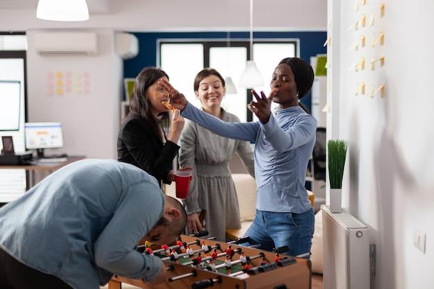 Vielfältiges team von freunden, die nach der arbeit den wettbewerb genießen und beim tischfußball spielen. lustige fröhliche aktivität zum feiern im büro mit tassen bier alkohol