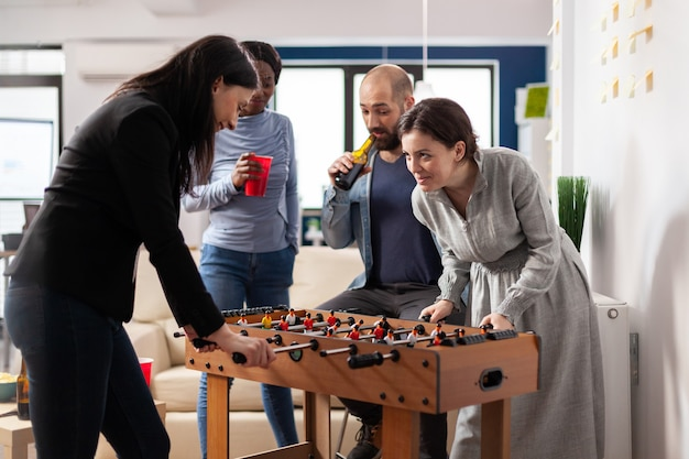 Vielfältiges team von kollegen, die nach der arbeit tischfußball-fußballspiel spielen. multiethnische gruppe, die lustige, fröhliche aktivitäten genießt, während sie im büro bieralkohol aus tassenflaschen trinkt