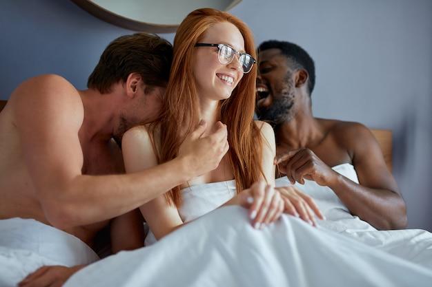 Vielfältiges trio, das sich im schlafzimmer liebt