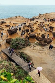 Vielfalt der touristen im yehliu geopark, einem kap an der nordküste taiwans. eine landschaft aus waben- und pilzfelsen, die vom meer erodiert wurde.