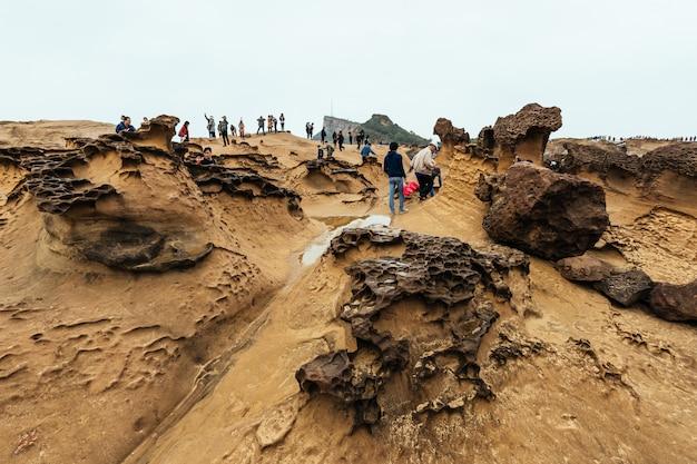 Vielfalt der touristen zu fuß in yehliu geopark, einem kap an der nordküste von taiwan. eine landschaft aus waben- und pilzfelsen, die vom meer abgetragen werden.