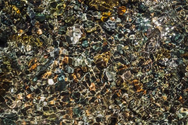 Vielfarbige detaillierte textur des steinigen bodens des transparenten baches in der nähe. sauberes wasser in mountain creek. bunter hintergrund der glatten steine im flussstrom mit kopienraum.