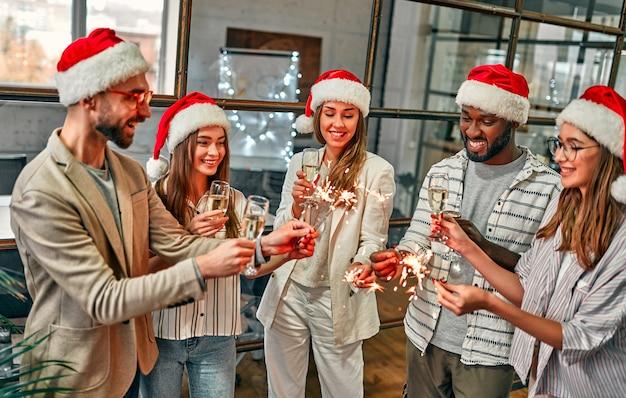 Vielpunkt junge junge kreative feiern den urlaub mit wunderkerzen in einem modernen büro. eine gruppe junger geschäftsleute trinkt champagner