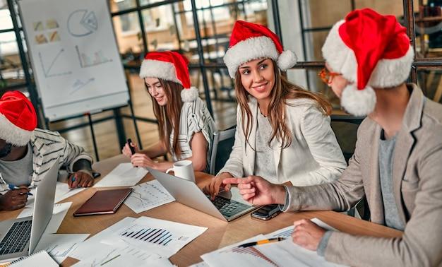 Vielpunkt junge junge leute feiern urlaub im modernen büro. eine gruppe junger geschäftsleute sitzt am letzten arbeitstag in weihnachtsmützen.