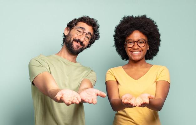 Vielpunktpaar von freunden, die glücklich mit freundlichem, selbstbewusstem, positivem blick lächeln, ein objekt oder konzept anbieten und zeigen