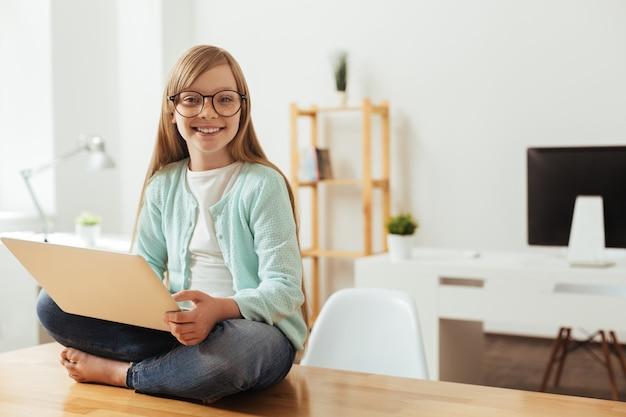 Vielversprechende dame. produktives intelligentes aktives kind, das sich wohl fühlt, während es seinen laptop benutzt