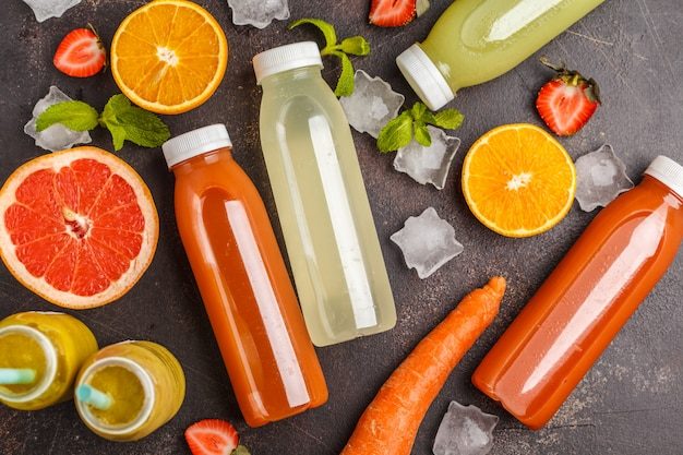 Vielzahl bunte smoothies oder saftflaschen von beeren, obst und gemüse, draufsicht, dunkler tisch. detox-programm, konzept für einen gesunden lebensstil.