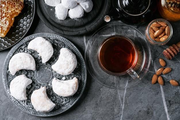 Vielzahl der traditionellen griechischen bonbonplätzchen kourabiedes und akanes lukum im zuckerpuder diente mit honig