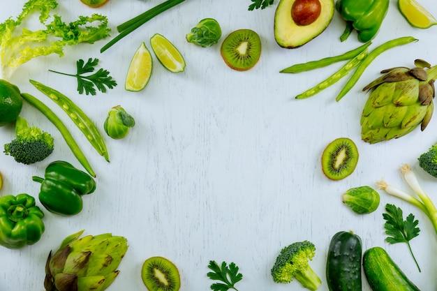 Vielzahl des grünen gemüses und der früchte auf einem arbeitsplatzarbeitsplatz des holztischs kochen mit frischem