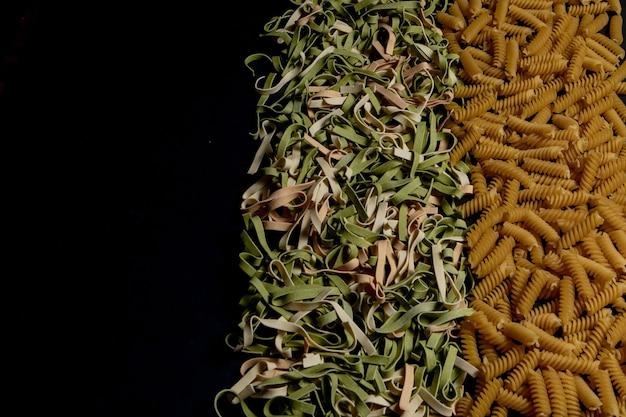 Vielzahl von arten und formen trockener italienischer nudeln. hintergrund oder textur der italienischen makkaroni-rohkost: nudeln, spaghetti, nudeln in form einer spirale.
