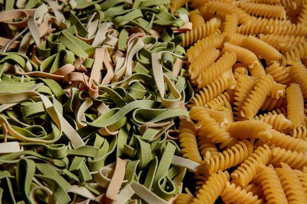 Vielzahl von arten und formen von trockenen italienischen nudeln. hintergrund oder textur der italienischen makkaroni-rohkost: nudeln, spaghetti, nudeln in form einer spirale.