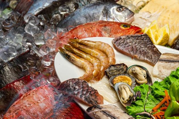 Vielzahl von fischen auf eis auf einem markt.