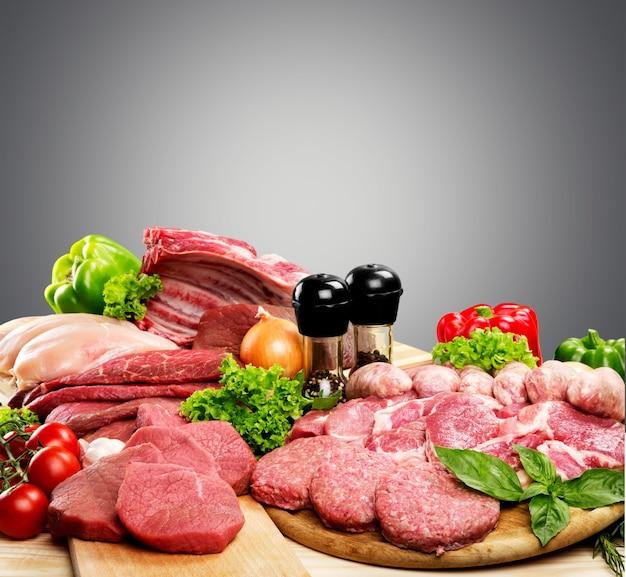 Vielzahl von fleisch und gemüse auf holztisch mit weichem grauem hintergrund