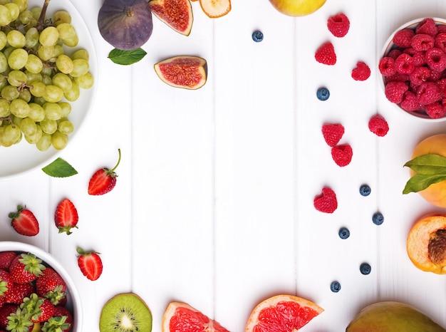 Vielzahl von früchten und beeren auf weißem holztisch, ansicht von oben