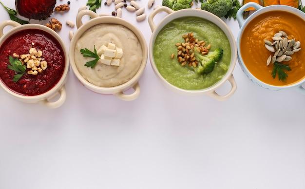 Vielzahl von gemüsecremesuppen mit brokkoli, weißen bohnen, rüben und kürbis, zutaten für suppe, konzept für gesunde ernährung, nahaufnahme, draufsicht, platz für text