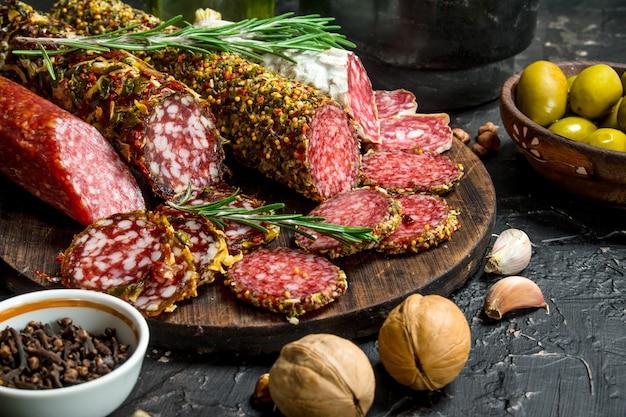 Vielzahl von geräucherter salami mit oliven, kräutern und gewürzen auf schwarzem rustikalem tisch.