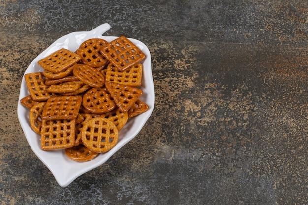 Vielzahl von gesalzenen crackern auf blattförmigem teller.