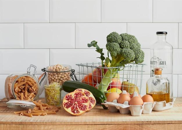 Vielzahl von gesunden lebensmitteln auf einem holztisch mit einem weißen fliesenhintergrund. gemüse, obst, eier, getreide