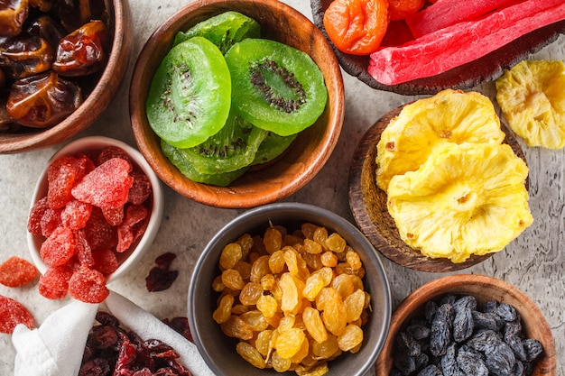 Vielzahl von getrockneten früchten in schalen. datteln, rosinen, getrocknete aprikosen und exotische getrocknete ananas, papaya und kiwi, draufsicht.