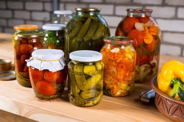 Vielzahl von gläsern mit konserviertem gemüse, frisch eingelegten gurken, paprika und tomaten auf holztisch