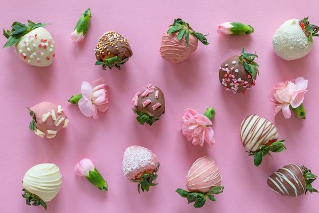 Vielzahl von handgemachten erdbeeren mit schokoladenüberzug mit verschiedenen belägen und blumen auf rosa hintergrund