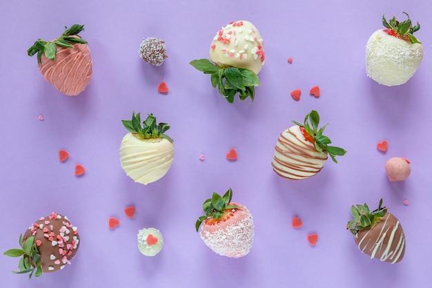 Vielzahl von handgemachten erdbeeren mit schokoladenüberzug und verschiedenen belägen auf lila hintergrund