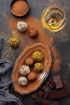 Vielzahl von hausgemachten dunklen schokoladentrüffeln mit kakaopulver, pistazien, mandeln in dunkelbrauner textur