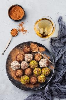 Vielzahl von hausgemachten dunklen schokoladentrüffeln mit kakaopulver, pistazien, mandeln in hellgrauer textur