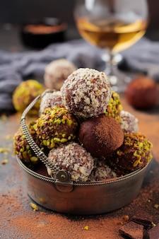 Vielzahl von hausgemachten dunklen schokoladentrüffeln mit kakaopulver, pistazien, mandeln