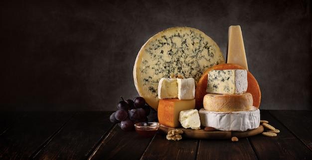 Vielzahl von käse auf einem hölzernen brett mit nüssen und honig