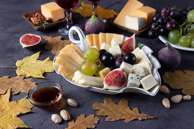 Vielzahl von käse und früchten auf grauem tisch. vorspeise zum erntedankfest.