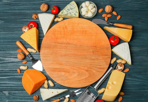 Vielzahl von käse und nüssen rund um das schneidebrett auf holzuntergrund