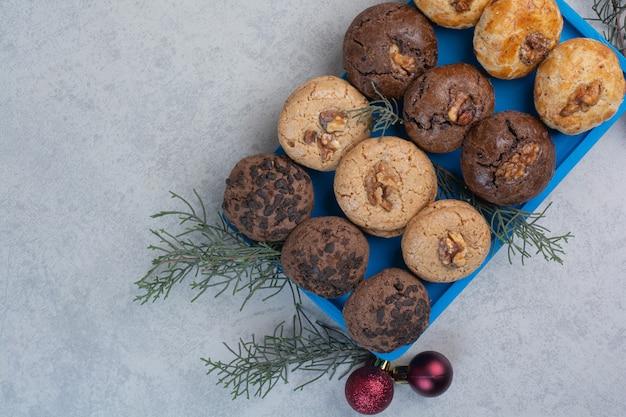 Vielzahl von keksen auf blauem teller mit weihnachtskugeln