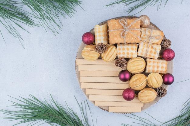 Vielzahl von keksen und weihnachtsschmuck auf holzbrett.