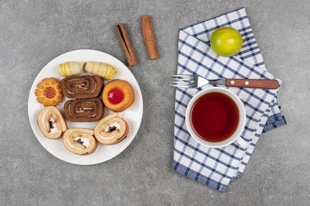 Vielzahl von köstlichen keksen auf weißem teller mit tasse tee