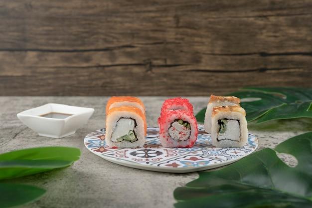 Vielzahl von leckeren sushi-rollen und grünen blättern auf steinoberfläche.
